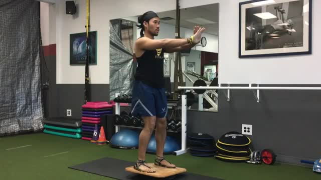 Male Balance Board Squat demonstration