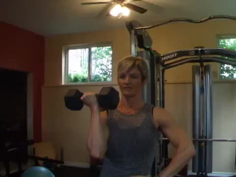 Female One Arm Standing Arnold Press demonstration